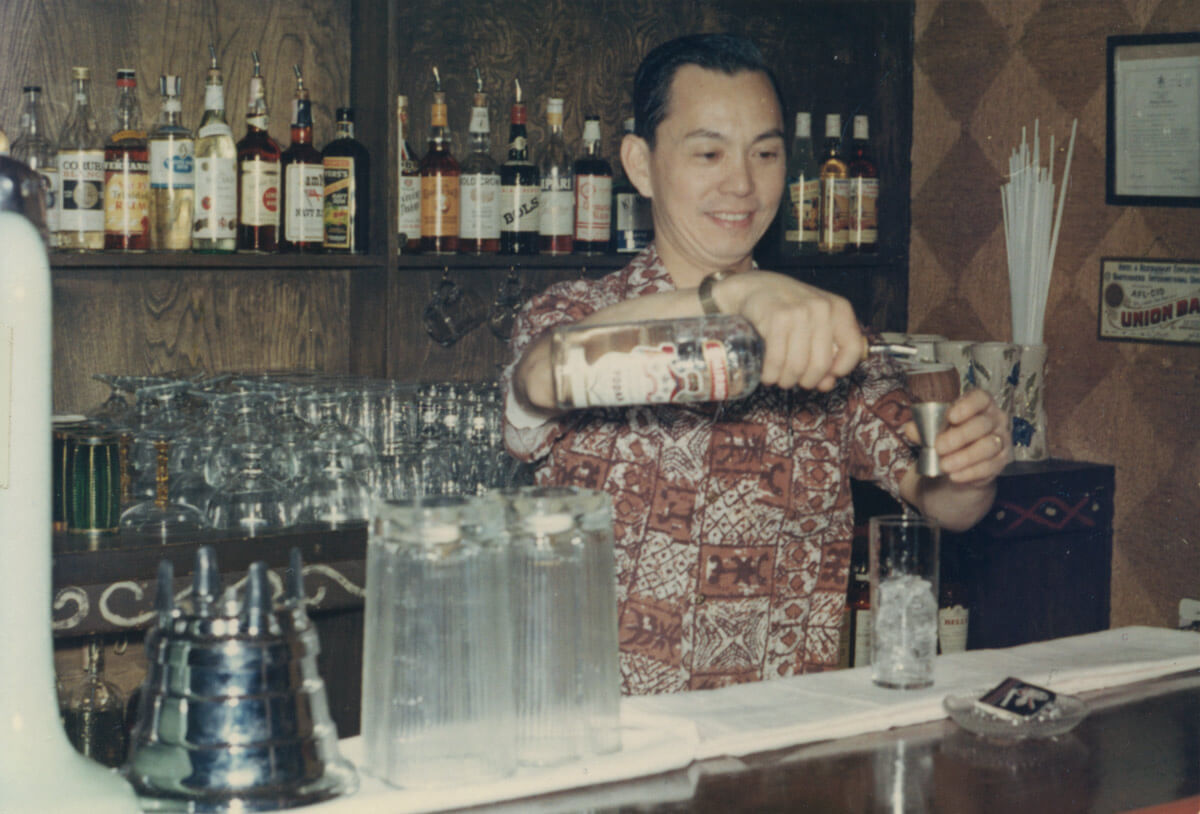 Chinese-Canadian man pours alcohol in a well stocked basement bar.