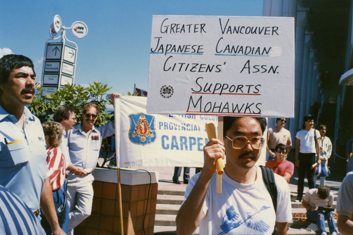 "Man at protest holding sign that says ""Greater Vancouver Japanese Canadian Citizens Assn. Supports Mohawks""."